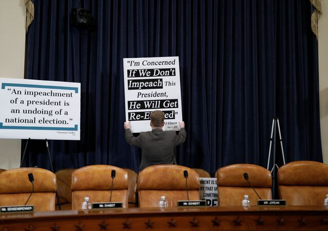 A Republican staff member adjusts a sign behind Republican seats on the dais at the first House Judiciary Committee hearing on the impeachment inquiry into U.S. President Donald Trump