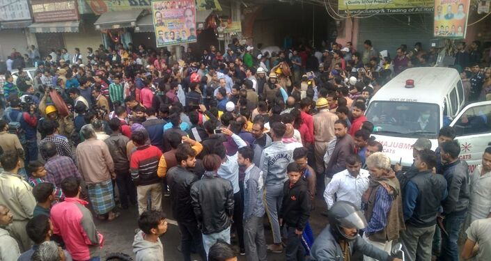 People gather on the street as a massive blaze breaks out at a factory in New Delhi's Anaj Mandi district