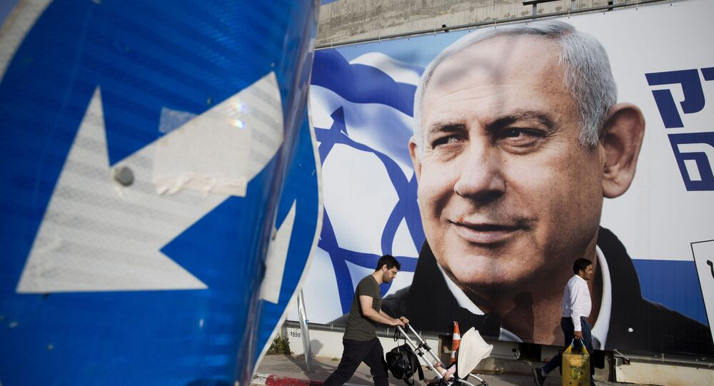 FILE - In this 7 April 2019 file photo, a man walks by an election campaign billboard showing Israel's Prime Minister Benjamin Netanyahu, the Likud party leader, in Tel Aviv, Israel.