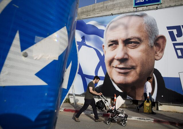FILE - In this April 7, 2019 file photo, a man walks by an election campaign billboard showing Israel's Prime Minister Benjamin Netanyahu, the Likud party leader, in Tel Aviv, Israel.