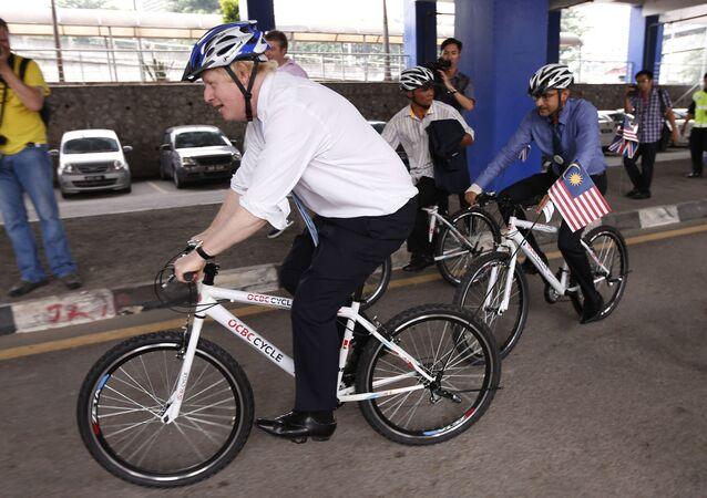 Boris Johnson rides a bicycle on a city tour in downtown Kuala Lumpur, Malaysia