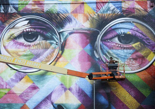 A graffiti artist works on a huge mural of former Beatle John Lennon