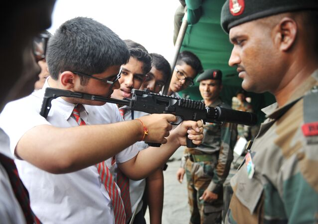 An Indian army officer watches as a school student checks the MP9 machine pistol during the display of arms and military equipment at the Polo Ground in Secunderabad, the twin city of Hyderabad, on September 29, 2018