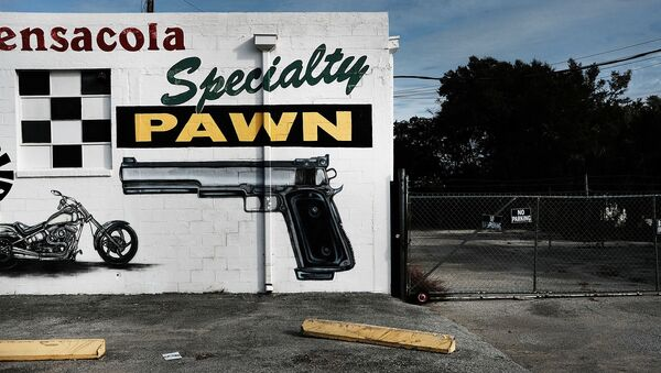 A pawn shop wall is painted with guns and other items in a struggling neighborhood in Pensacola, Florida, 3 December 2016. - Sputnik International