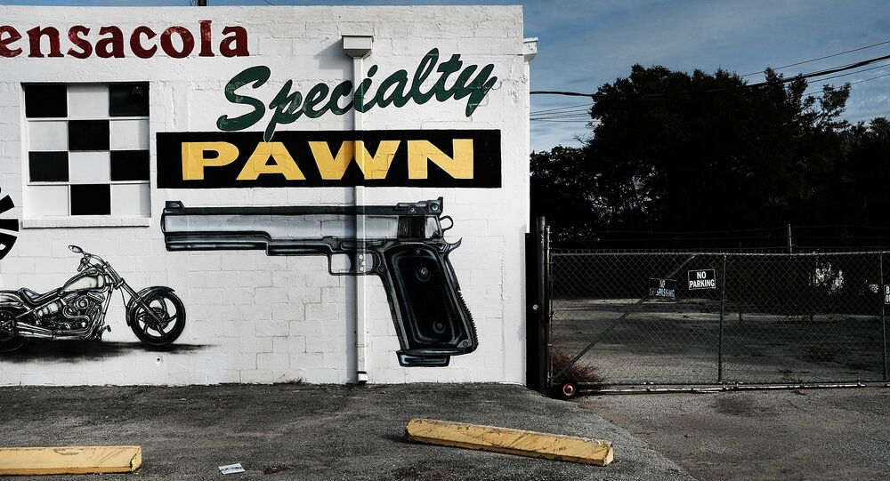 A pawn shop wall is painted with guns and other items in a struggling neighborhood in Pensacola, Florida, 3 December 2016.