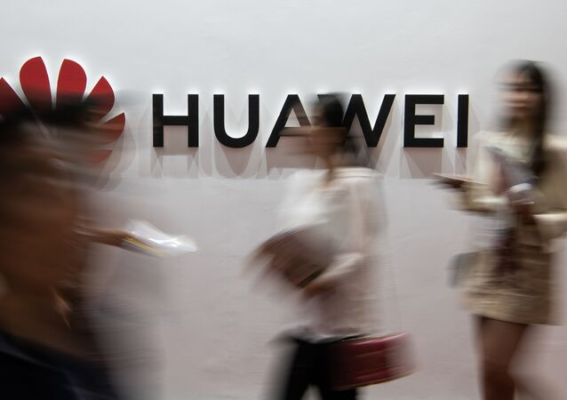 (FILES) In this file photo taken on August 2, 2019 people walk past a Huawei logo during the Consumer Electronics Expo in Beijing. - Chinese tech giant Huawei, facing US criminal charges and economic sanctions, is planning to relocate its telecommunications research from the United States to Canada, founder Ren Zhengfei said in an interview published on December 3, 2019
