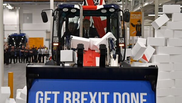 Britain's Prime Minister and Conservative party leader Boris Johnson drives a Union flag-themed JCB, with the words Get Brexit Done inside the digger bucket, through a fake wall emblazoned with the word GRIDLOCK, during a general election campaign event at JCB construction company in Uttoxeter, Staffordshire, on December 10, 2019. - Sputnik International