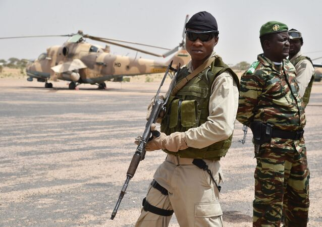 Niger army soldiers stand guard next to a Niger's Air Force Mi-35P attack helicopter on the tarmac in Diffa, southeastern Niger