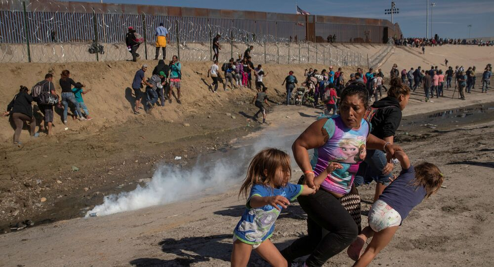 Maria Meza, a 40-year-old migrant woman from Honduras, part of a caravan of thousands from Central America trying to reach the United States, runs away from tear gas with her five-year-old twin daughters Saira Mejia Meza (L) and Cheili Mejia Meza (R) in front of the border wall between the U.S and Mexico, in Tijuana, Mexico, November 25, 2018