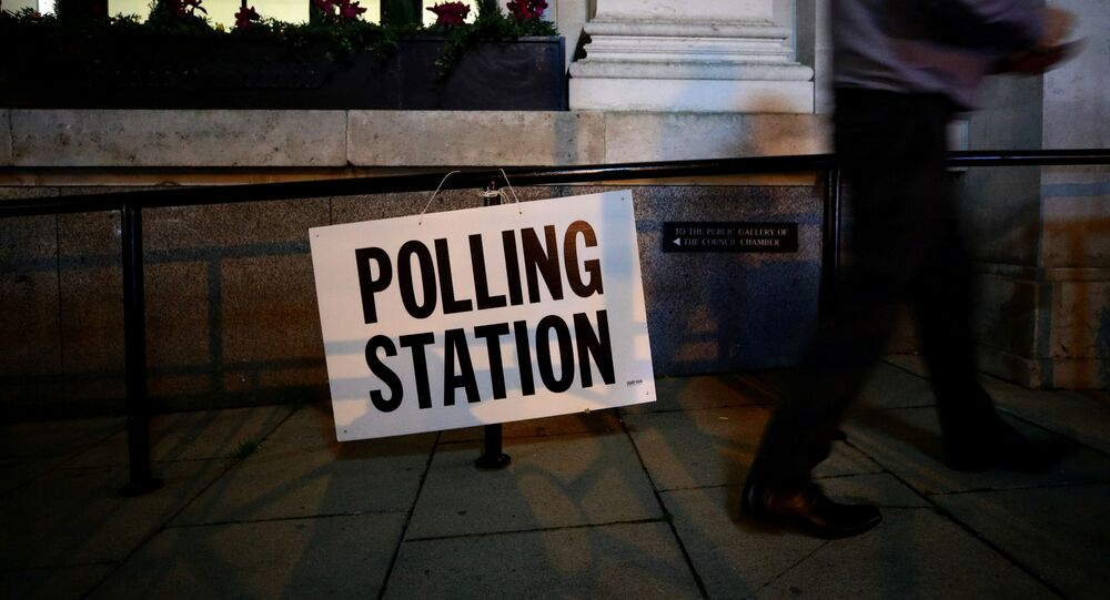 A man walks past a sign outside a polling station on general election day in London, Britain, December 12, 2019