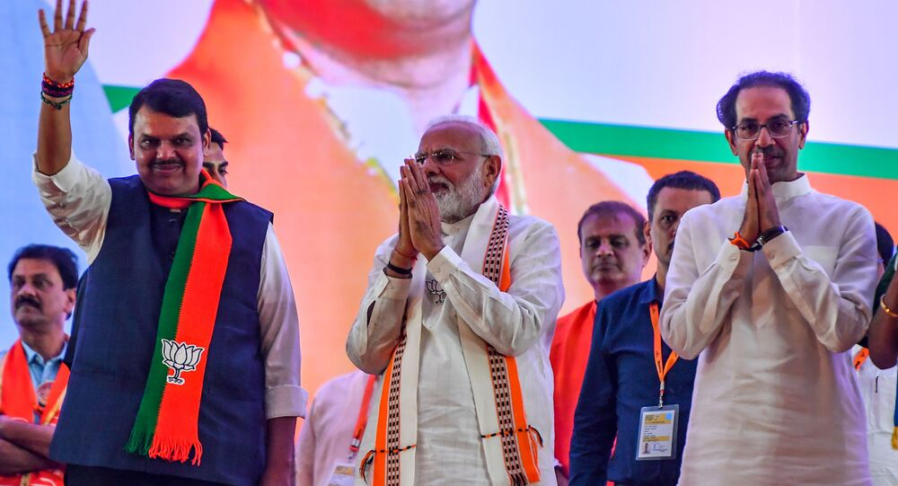 India's Prime Minister Narendra Modi (C) gestures along with Hindu right-wing party head Shiv Sena Chief Uddhav Thackeray (R) and Chief Minister of the state Devendra Fadnavis (L) as they attend a public rally in the run up to the Maharashtra state assembly elections, in Mumbai on 18 October 2019