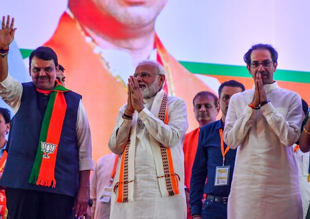 India's Prime Minister Narendra Modi (C) gestures along with Hindu right-wing party Shiv Sena Chief Uddhav Thackeray (R) and Chief Minister of the state Devendra Fadnavis (L) as they attend a public rally in the run up to the Maharashtra state assembly elections, in Mumbai on October 18, 2019