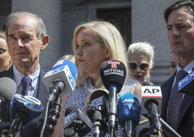 In this 27 August 2019, photo, Virginia Roberts Giuffre, centre, who says she was trafficked by sex offender Jeffrey Epstein, holds a news conference outside a Manhattan court where sexual assault claimants invited by a judge addressed a hearing following Epstein's jailhouse death in New York