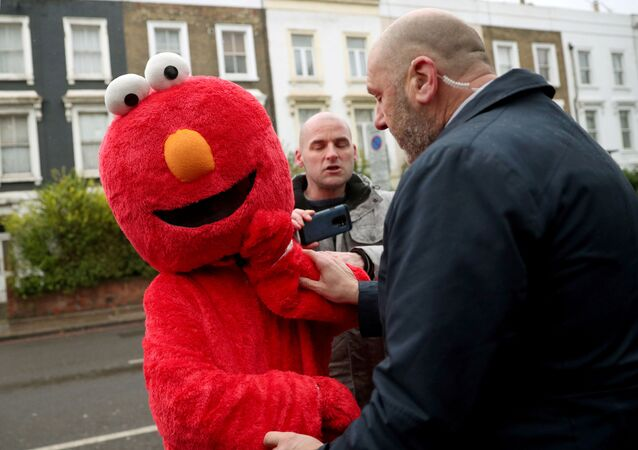 A member of Britain's opposition Labour Party leader Jeremy Corbyn's security detail argues with a person dressed as Sesame Street character Elmo as Corbyn returns from a polling station after voting in the general election in London, Britain, December 12, 2019