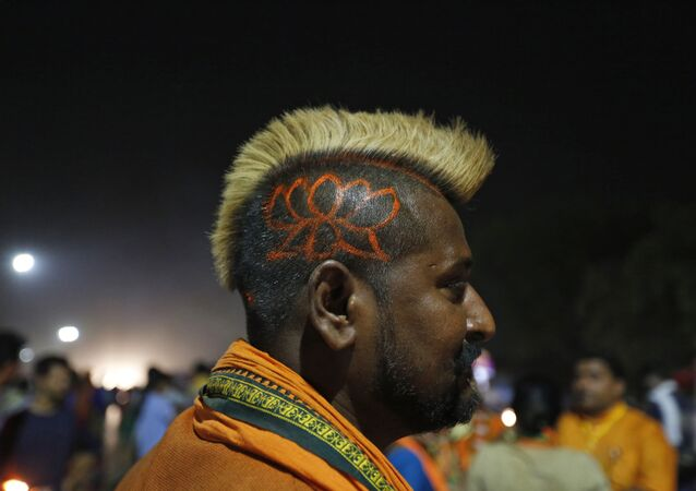A supporter of India's Bharatiya Janata Party (BJP) Nagraj Singh displays a haircut sporting the party's symbol during an election campaign rally in Prayagraj, India, Thursday, May 9, 2019