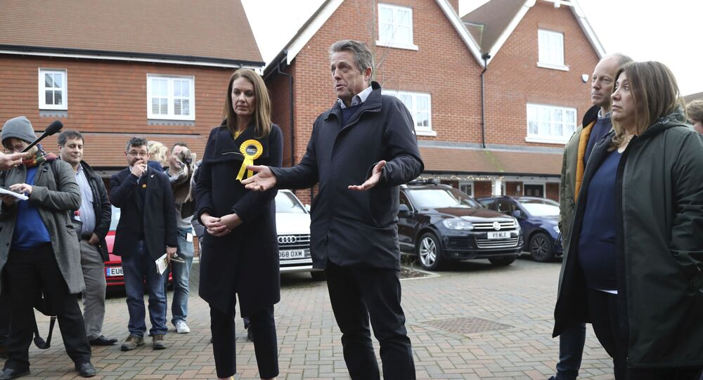 In this photo dated Saturday, Dec. 7, 2019, British actor Hugh Grant poses for a photo with Liberal Democrats Party election candidate Monica Harding, during an election campaign visit in the Esher and Walton constituency, Walton-on-Thames, England