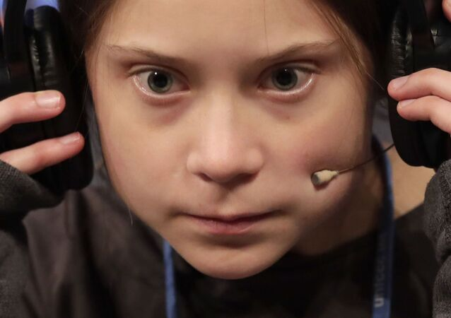 Climate activist Greta Thunberg adjusts hrt headphones during a press conference in Madrid, Friday, 6 December 2019