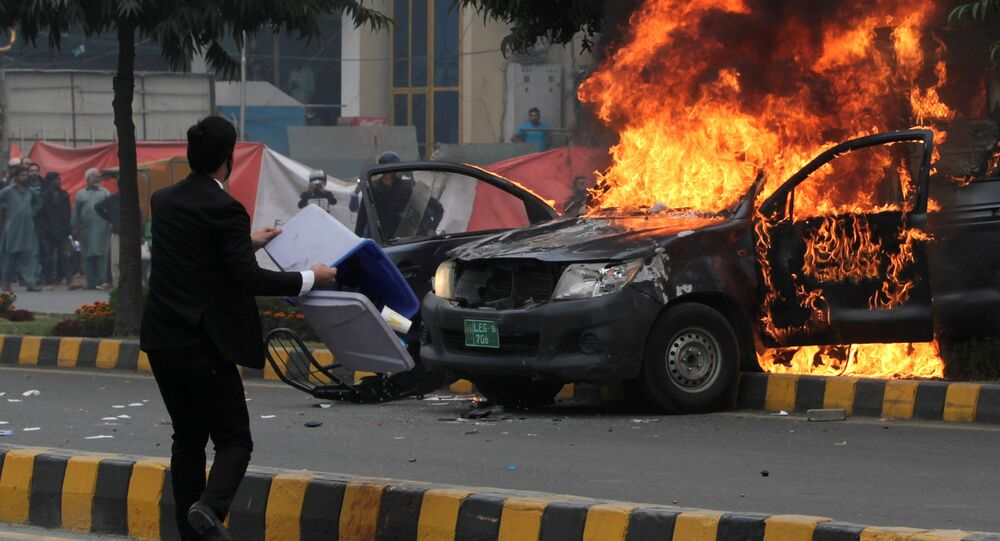 A lawyer throws trash bin towards police near a vehicle set on fire outside the Punjab Institute of Cardiology (PIC) in Lahore, Pakistan December 11, 2019