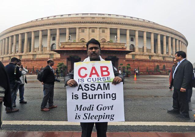 An Indian Lawmaker from Congress party, Abdul Khaleque holds a banner in protest against the Citizenship (Amendment) Bill at the Parliament House, in New Delhi, India, Friday, Dec. 13, 2019