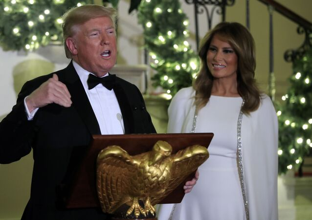 President Donald Trump speaks in the Grand Foyer of the White House during the Congressional Ball, Thursday, Dec. 12, 2019 in Washington, as First Lady Melania Trump watches.