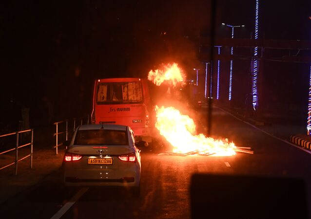 In this photo taken on December 12, 2019 a bus and car drive past a burning barricade set up by demonstrators following protests against the Citizenship Amendment Bill (CAB) in Guwahati.