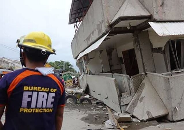 Rescuers near a collapsed building in Padada, Davao del Sur province, southern Philippines