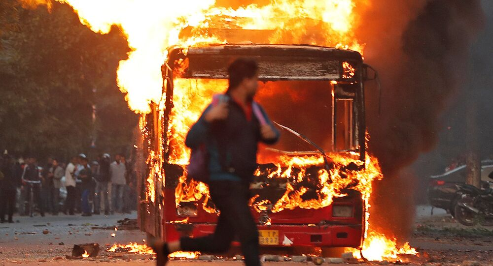 A man runs past a burning bus that was set on fire by demonstrators during a protest against a new citizenship law, in New Delhi, India, December 15, 2019