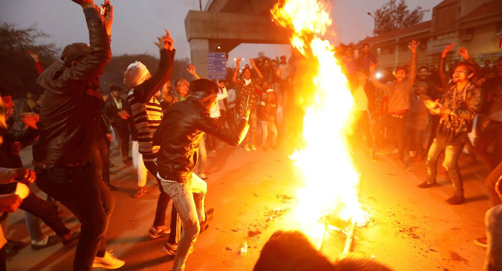 Demonstrators burn an effigy depicting Prime Minister Narendra Modi during a protest against the new citizenship law outside Jamia Millia Islamia university in New Delhi, India, 16 December 2019.
