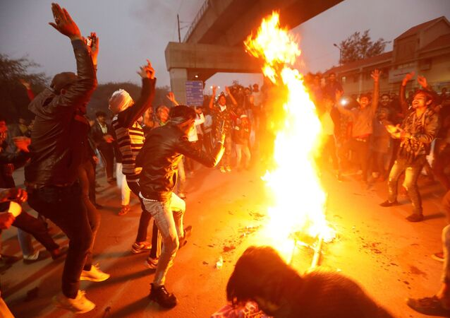 Demonstrators burn an effigy depicting Prime Minister Narendra Modi during a protest against a new citizenship law, outside Jamia Millia Islamia university in New Delhi, India, December 16, 2019.