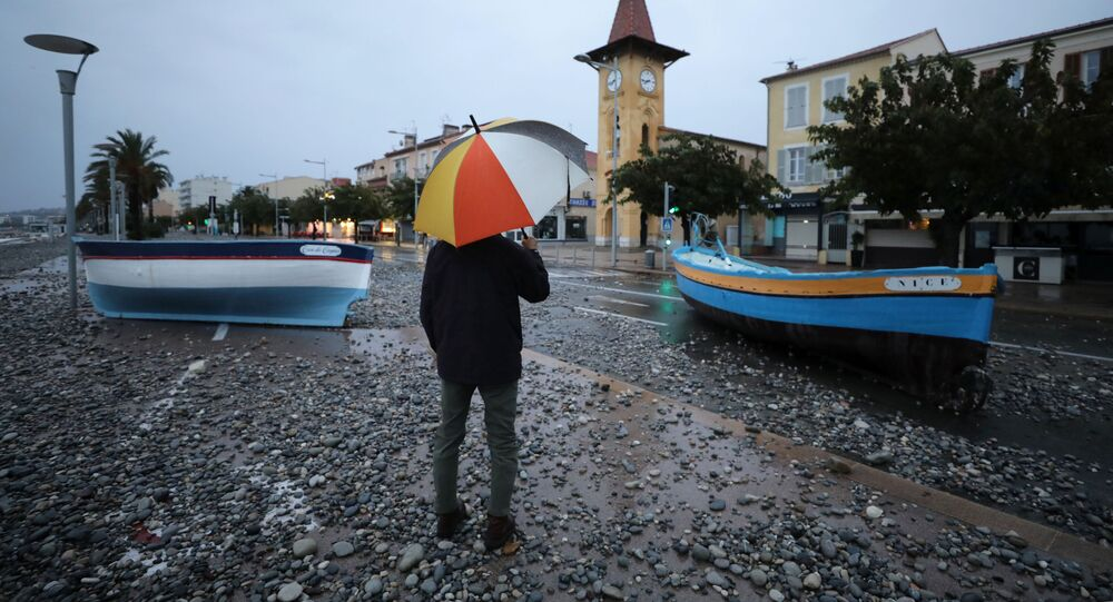 A man looks at fishing boats stuck on a street after heavy rain fall in Cagnes-sur-Mer, France