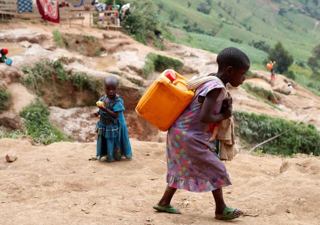 A girl carries a container of water at a coltan mine in Kamatare, Masisi territory, North Kivu Province of Democratic Republic of Congo