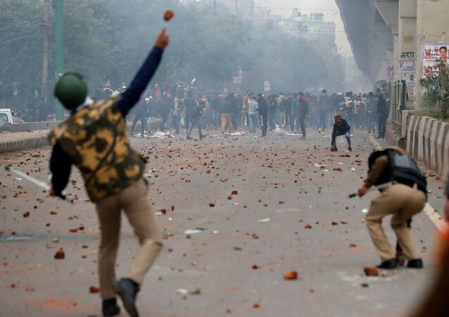 A riot police officer throws a piece of brick towards demonstrators during a protest against a new citizenship law in Seelampur, a neighbourhood of Delhi, India 17 December 2019