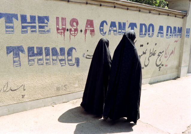 Two Iranian women wearing chadors walk past an anti-American slogan in a street of the Djarmaran district where lived Ayatollah Khomeini on July 30, 1989