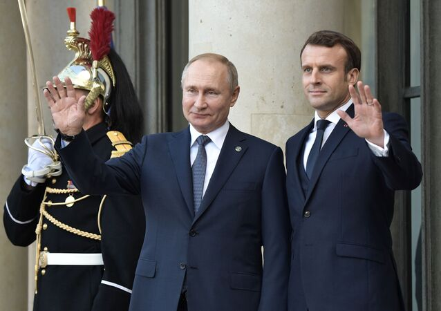 Russian President Vladimir Putin and French counterpart Emmanuel Macron during the official ceremony at the Elysee Palace on 9 December 2019
