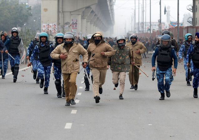 Policemen are chased by demonstrators during a protest against the new citizenship law in Seelampur, an area of Delhi, India on 17 December 2019.