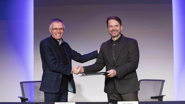 Carlos Tavares of Groupe PSA (left) and Mike Manley of FCA (right) shake hands after signing merger agreement on 18 December 2019 - Sputnik International
