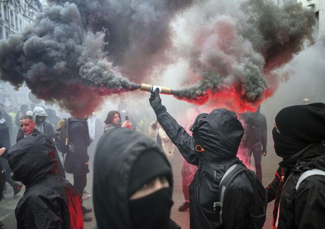 A protester holds up a flare during a demonstration in Lyon, central France, Tuesday, Dec. 17, 2019. Workers at the Eiffel Tower, teachers, doctors, lawyers and people from across the French workforce walked off the job Tuesday to resist a higher retirement age, or to preserve a welfare system they fear their business-friendly president wants to dismantle. (AP Photo/Laurent Cipriani)