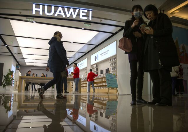 In this Nov. 20, 2019, photo, people stand outside of a Huawei store at a shopping mall in Beijing