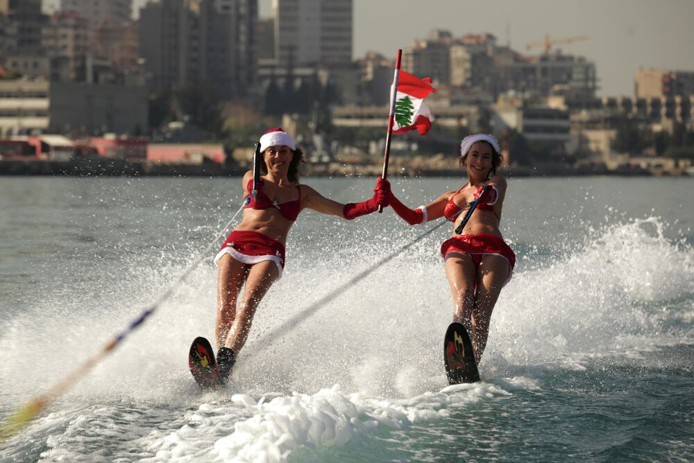 Two Lebanese women wearing Santa Claus outfits and waving their national flag water ski during a show in the bay of Jounieh, 20 km north of Beirut, on 24 December 2013.