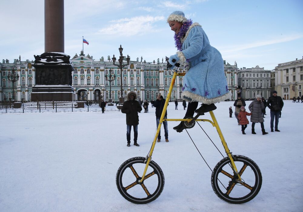 A woman wearing a Snow Maiden costume rides a bike during a celebration of Old New Year at Dvortsovaya (Palace) Square in St. Petersburg, Russia, Sunday, 13 January 2019. Russian people celebrate so-called Old New Year, which arrives on the 14th  of January and coincides with the first of the month under the Julian calendar formerly used by Russia and still observed by its Orthodox Church. For most Russians, Old New Year is just a way to prolong the New Year's celebrations.