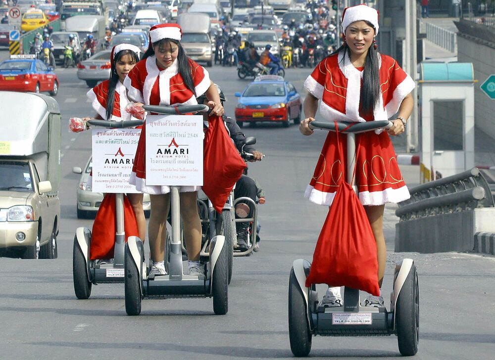 Female hotel workers dress in Santa Claus costumes and ride Segways to give presents to residents in the centre of Bangkok, 16 December 2005. The campaign is one of the activities set up to promote the Christmas festival before it is celebrated in Thailand.