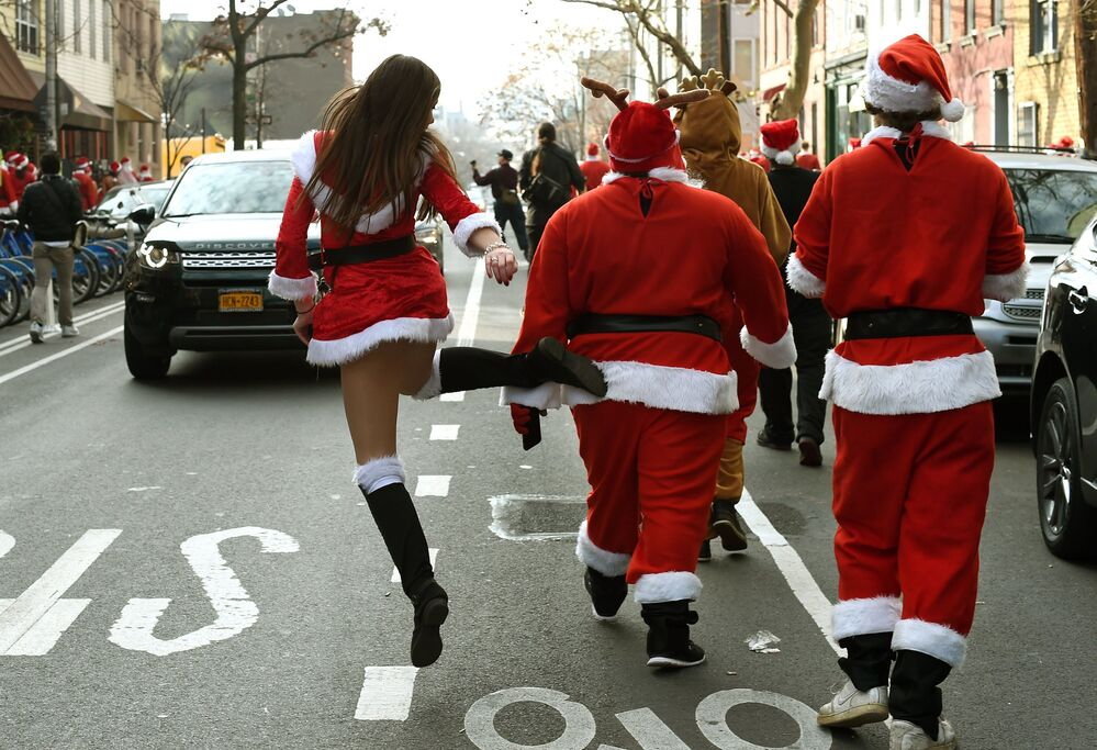 People dressed as Santa Claus and other holiday related outfits start their parade after meeting in Brooklyn's McCarren Park during the SantaCon 2015 in New York City 12 December 2015, the 21st anniversary of the event that sees hundreds of people dress as Father Christmas.