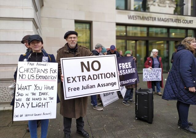 Supporters of Julian Assange hold placards outside Westminster Mags Court 19 December 2019