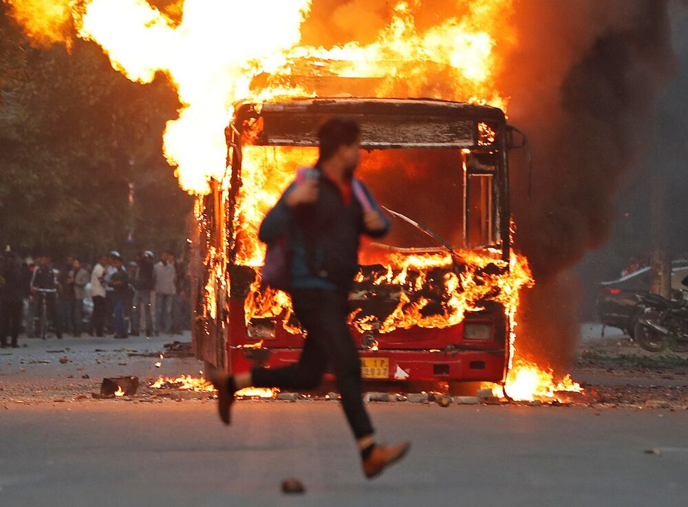 A man runs past a burning bus that was set on fire by demonstrators during a protest against a new citizenship law, in New Delhi, India, 15 December  2019.