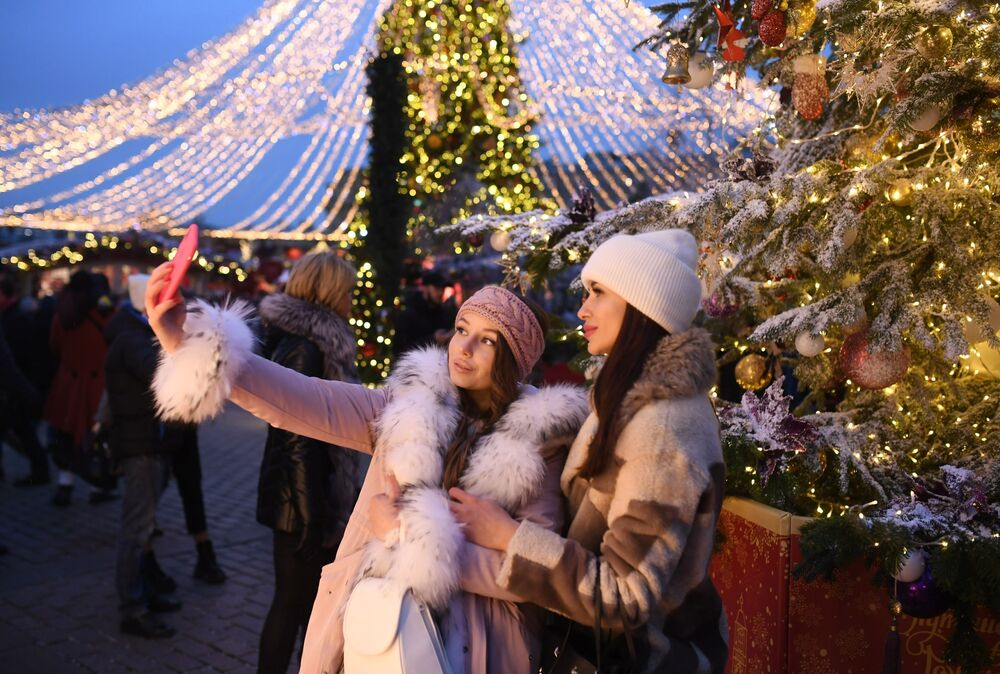 Girls are photographed at the 'Travel to Christmas' festival on Manezhnaya Square in Moscow.