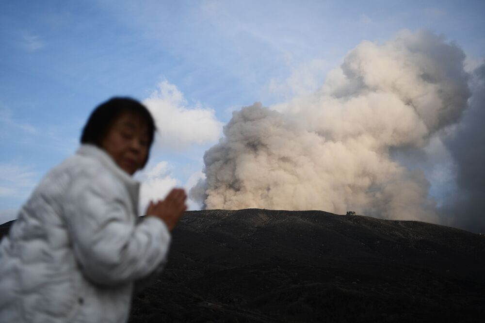 A woman stands near Mount Aso, an active volcano, in the city of Aso, Japan in Kumamoto prefecture on 14 December 2019. The 1,592-metre (5,253-foot) volcano is a popular tourist spot; its huge caldera dominates the southwest of Japan's main island of Kyushu.