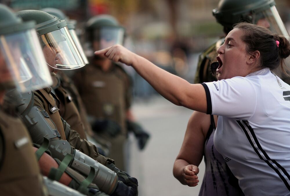 A woman argues with a riot policeman during a protest against Chile's government in Santiago, Chile 15 December 2019.