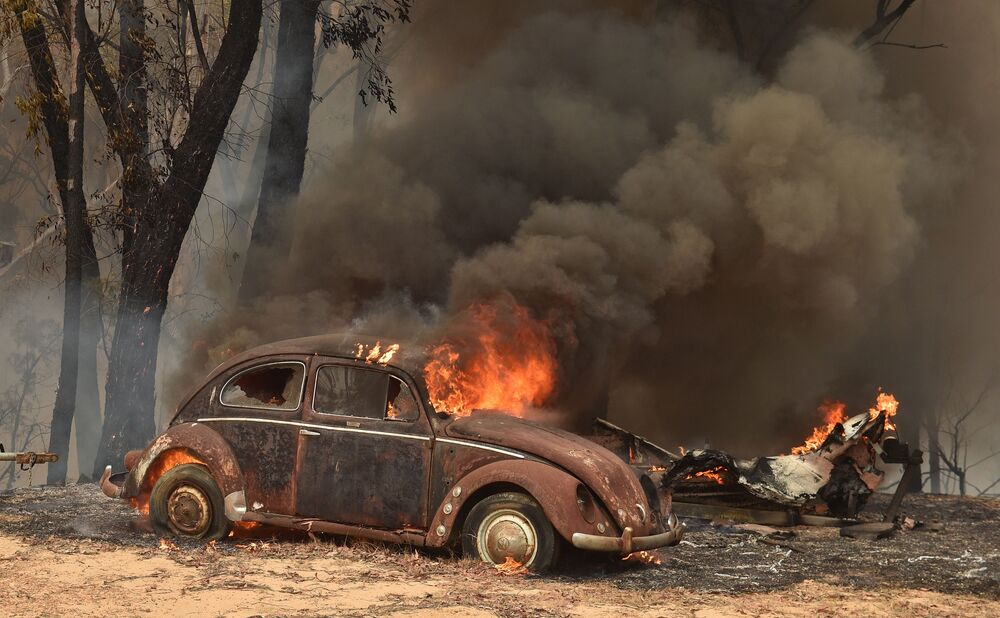 An old car burns from bushfires in Balmoral, 150 kilometres southwest of Sydney on 19 December 2019. - A state of emergency was declared in Australia's most populated region on 19 December  as a record heat wave fanned unprecedented bushfires.