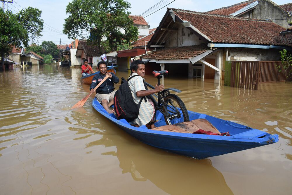 Residents commute by boat through a flooded road in Dayeuhkolot, Bandung in Indonesia's West Java province on 18 December 2019, after heavy rains flooded the Citarum river.