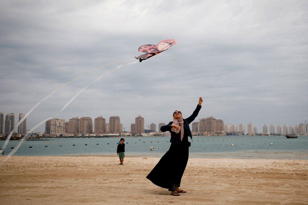 A Muslim woman flies a kite at Katara beach in Doha, Qatar on 13 December 2019.
